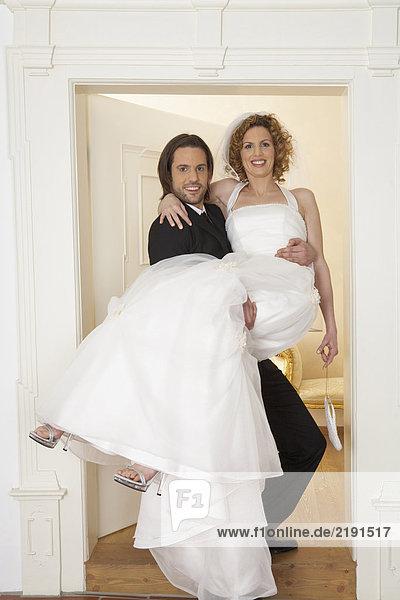 junger Bräutigam mit Braut über der Schwelle  Portrait