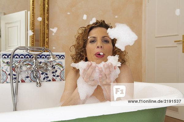 Frau bläst Schaum aus den Händen im Bad  Portrait