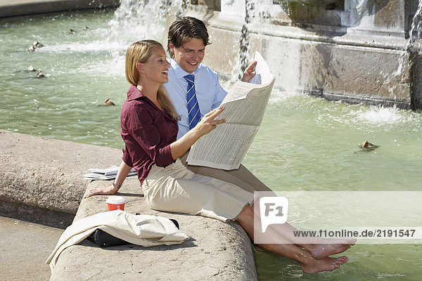 Geschäftsmann und Frau sitzen auf einem Springbrunnen und lesen zusammen lachend Zeitung.