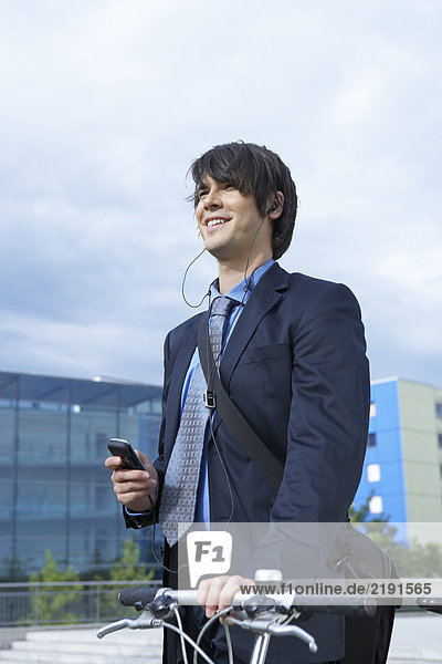 Businessman in park walking his bike with headset and mobile laughing.