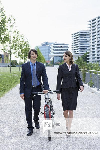 Businessman and woman walking in park he is walking his bike talking.