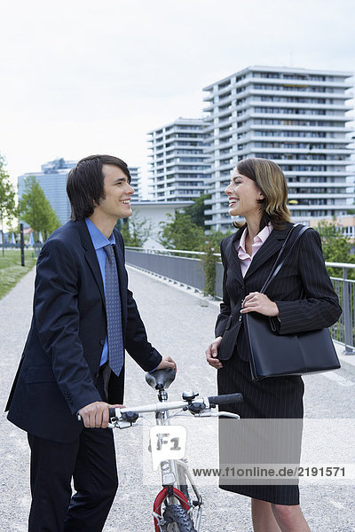 Businessman and woman talking in-between bike laughing.