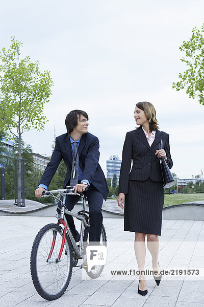 Businessman and woman talking she is walking him on bike laughing.