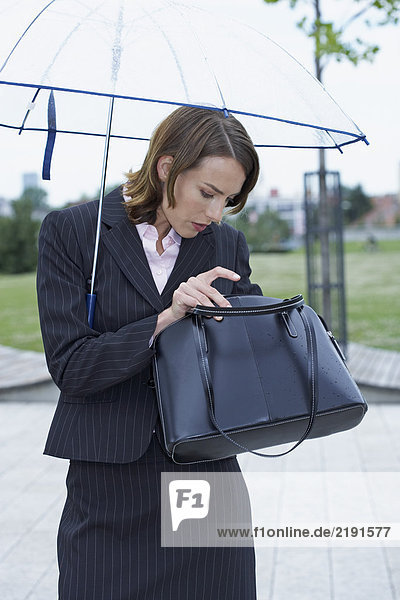 Businesswoman with umbrella fishing something out of handbag.