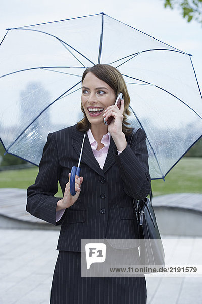 Businesswoman with umbrella on the mobile.