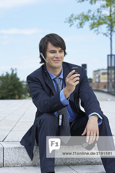 Businessman sitting on steps with headset looking at his mobile.