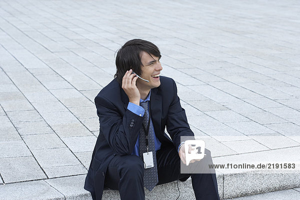 Businessman sitting on steps with headset and mobile talking looking into distance smiling.