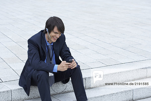 Businessman sitting on steps with headset looking at his mobile laughing.