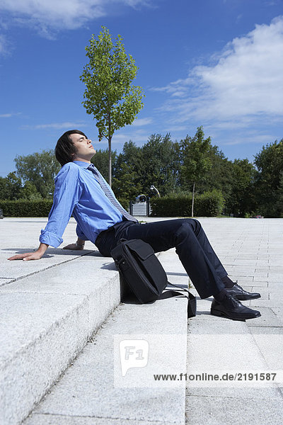 Businessman sitting on steps with laptop sunbathing smiling park in background.