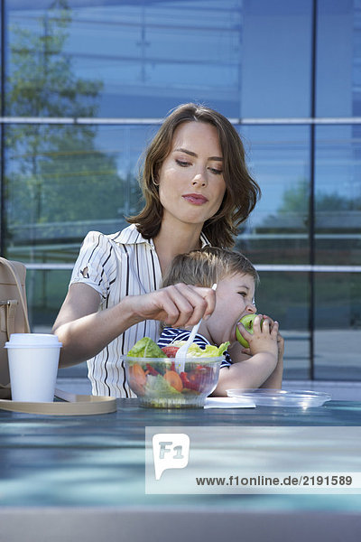 Businesswoman and her son on table in front of office outside she is eating salad to go her son eating apple.