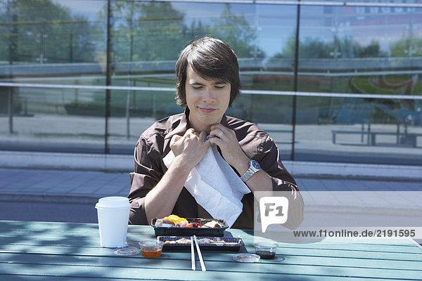 Businessman eating sushi outside using napkin.