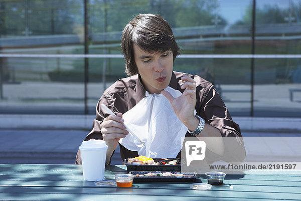 Businessman eating sushi outside with chopsticks licking off finger.