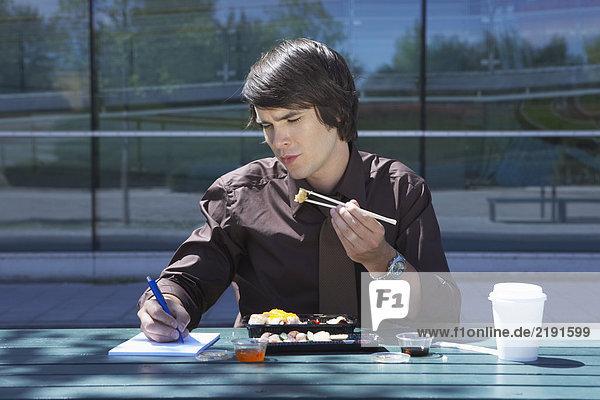 Businessman eating sushi outside while making notes.