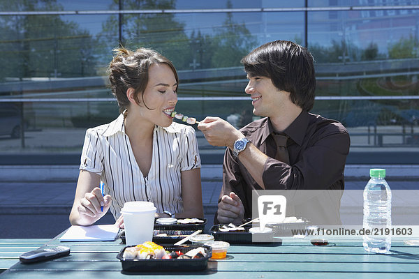 Couple eating sushi together outside while working.