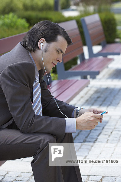 Businessman on bench with MP3 earpieces looking at his MP3.