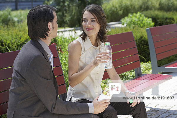 businessman and woman looking at each other with lunch on a bench outdoors