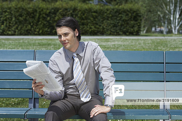 Businessman on bench with newspaper reading.