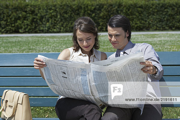 Businessman and woman on bench in park reading a newspaper together.
