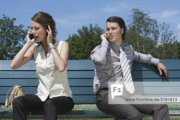 Businessman and women talking on cell phones while sitting on bench outside.