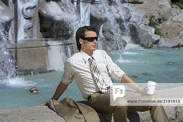 businessman sitting by fountain with coffee to go wearing sunglasses