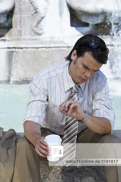 Businessman sitting on edge of fountain with coffee to go looking at his watch.