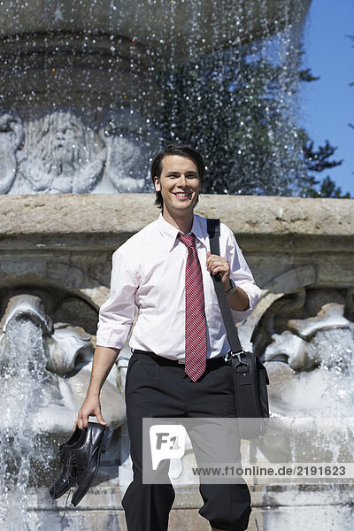Businessman standing in front of fountain with laptop bag and shoes in hand smiling.