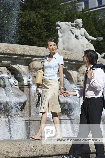 Young couple walking beside fountain holding hands.