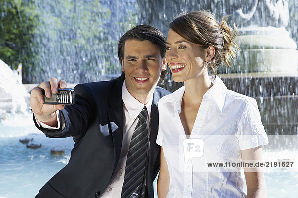Young couple taking picture together beside fountain.