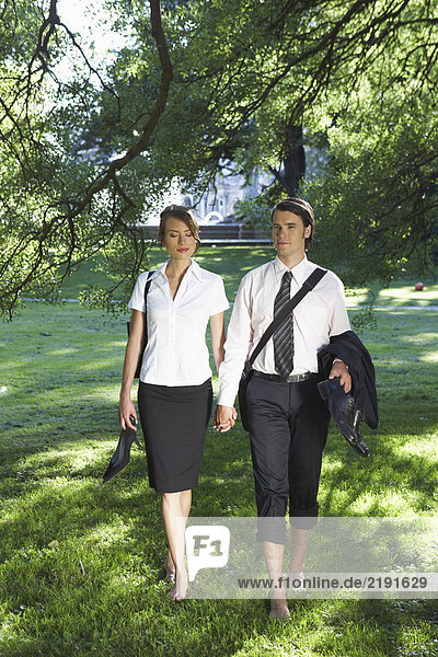 Young couple holding hands while walking in meadow barefoot.
