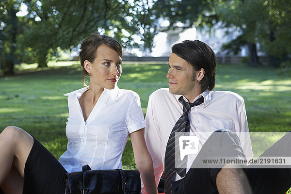 Businessman and woman sitting in meadow in park watching each other.
