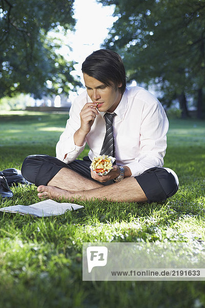 Businessman eating in park while reading.
