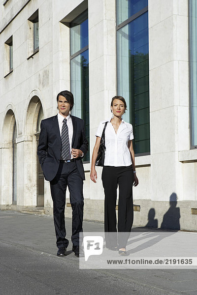 Businessman and woman walking on street in city frontal view.