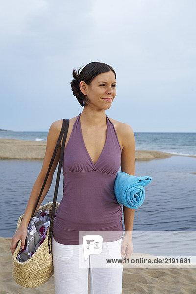 Junge Frau mit Strandtasche am Strand.