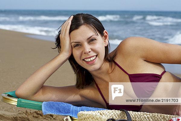 Young woman in bikini on beach lying in deck chair sea in background.