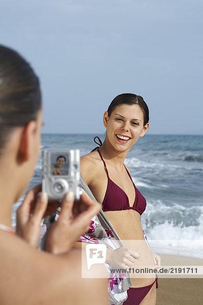 Zwei junge Frauen am Strand beim Fotografieren.