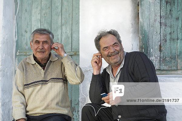 Zwei reife Männer teilen sich Kopfhörer und lachen.