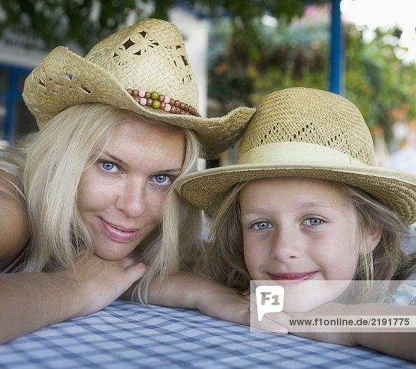 Frau mit jungem Mädchen in einem Restaurant im Freien lächelnd.