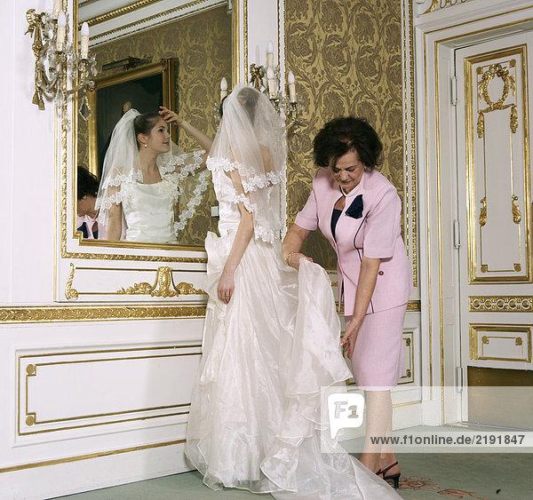 Mutter,  die das Hochzeitskleid auf der Braut anpasst