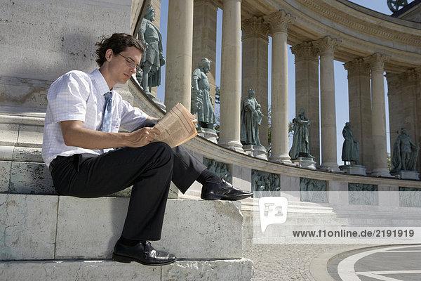 Geschäftsmann  der draußen Zeitung liest.