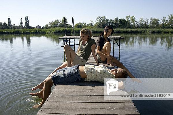 Drei junge Frauen auf einem Pier.