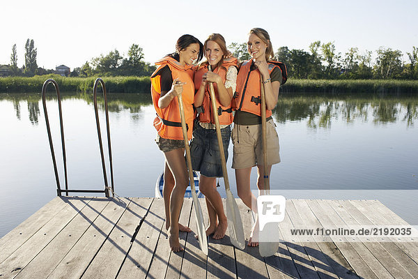 Three young women on a pier with oars.