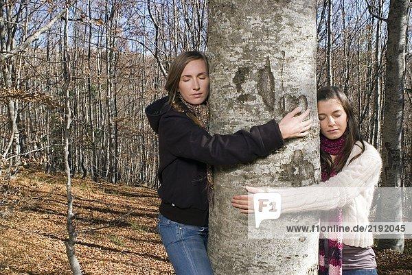 Zwei junge Frauen umarmen einen Baum.