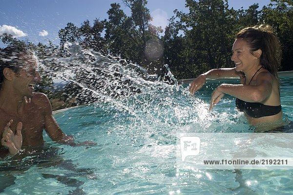 Pärchen spielen mit Wasser im Schwimmbad
