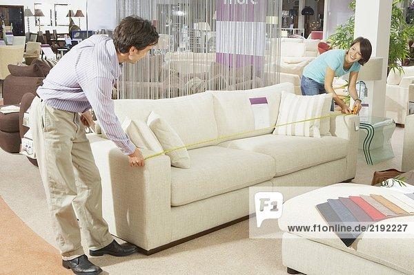 Ein Paar misst ein Sofa in einem Laden.