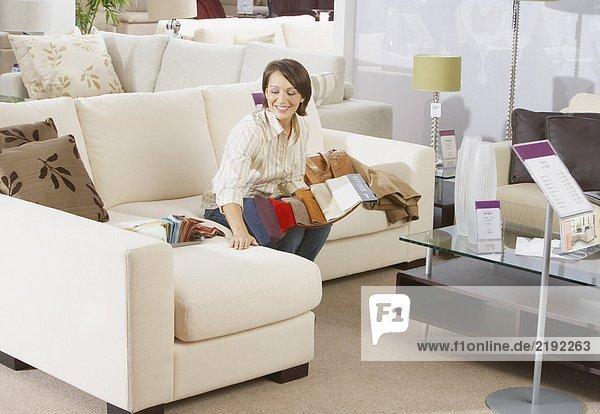 Frau sitzt auf dem Sofa im Möbelhaus.