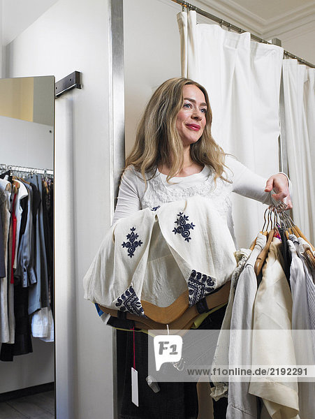Woman in changing room holding clothes  smiling