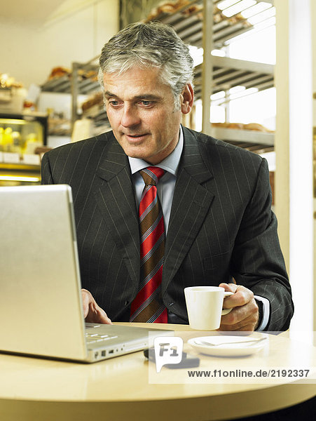 Mature businessman sitting in cafe using laptop