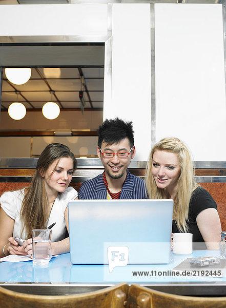 Drei Leute  die einen Laptop in einem Diner anschauen.