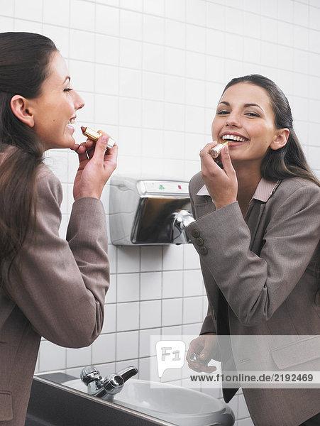 Frau spiegelt sich im Büro-Waschraumspiegel mit Make-up