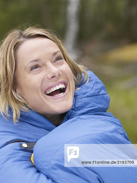 Woman with sleeping bag wrapped around her laughing.
